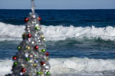 Christmas tree on beach (focus on waves in sea)