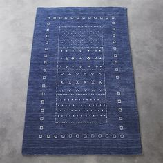 Shop game time hand-loomed rug.   Folk-inspired, indigo-dyed, soft and worn in—hand-loomed carpet steps up the style in any room.  Heathered blue base backdrops intricate white designs skillfully woven at the very end.