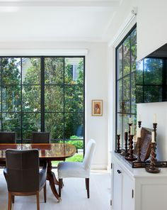 In the dining room, the thin frames of the steel and glass doors and windows dissolve in the white walls blurring the boundary between interior and exterior.