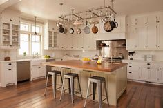 Sensational kitchen boasts a large stainless steel pot rack suspended over a beige kitchen island with beadboard trim topped with butcher block framing small prep sink paired with gooseneck faucet lined with Tolix Stools.