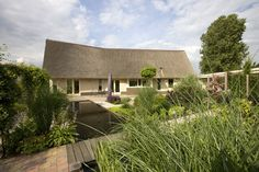 Een prominente rietgedekte villa, gebouwd in een heldere hoofdvorm. Het ontwerp is afgestemd op de bijzondere bouwlocatie.