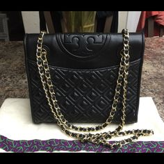 Tory Burch Black Quilted Leather Fleming Handbag STUNNING!!!! Authentic Tory Burch Black Quilted Genuine Leather Shoulder Bag with Gold Tone Hardware, Chain Link & Leather Shoulder Straps, Dual Exterior Pockets with Magnetic Closures, Black Woven Interior Lining, 3 pockets at interior walls, 1 zip. Snap closure at front face with Tory Burch All T logo atop. EXCELLENT Condition with very minor hardware scratches, minor interior creasing. SUPER CLEAN INSIDE & OUT! Dust Bag Included…