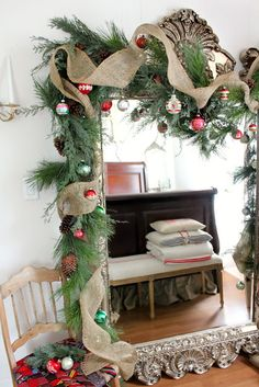 Burlap ribbons runs through pine on an ornate vintage mirror.  Old Christmas ornaments complete the look.