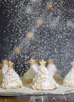Uma receita muito fácil para fazer bolinhos de árvore de Natal de coco.  Para o efeito adicionado, adicione uma varredura do açúcar pulverizado 'neve', algum brilho comestível e uma estrela do ouro.