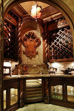 Walk-in wine cellar boasts custom made wrought iron doors which were inspired by the Antique crest piece from Europe built into the stone wall.