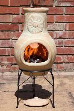 Yellow clay chimenea with a sun motif. This garden patio heater is hand made and hand painted and therefore colours and patterns may vary very slightly. The chimenea comes with a steel stand and a lid to prevent rain from entering the funnel.We always recommend covering when not in use and to take your chimenea inside in bad weather. Clay chimeneas have been used for centuries and have been created to only need a small fire, the clay will heat quickly and retain the heat for a long time.