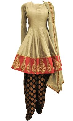 A unique grey anarkali salwar suit in raw silk base with gold zari embellished red border around the hem. It comes with a black banarsi salwar in georgette fabirc and is paired with a matching net dupatta with gold sequins embellished botis and border. This ravishing outfit will make you stand out from the crowd.