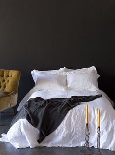dark charcoal bedroom walls with white sheets and a touch of yellow