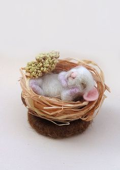 This cute baby mouse was hand made of wool using needle felt techniques. It sleeps in his little cot of a nutshell,filled with dry grass,