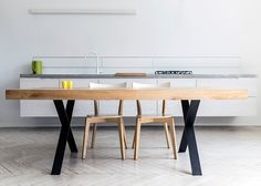 Polish design studio 5mm has created a collection of tables with heavy solid-oak tops balanced on slim powder-coated steel bases.