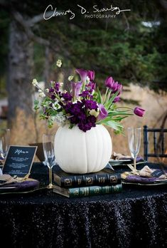 Brides.com: . Feeling the Halloween look? This dark and moody table setting is your inspiration. Black sequins, vintage books, and plum accents scream deep romance — and really make a white pumpkin pop.