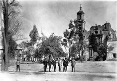 Un grupo de personas posan para la cámara frente a la iglesia de San Gabriel Arcángel, en el pueblo de Tacuba, cuando tenía una plaza despejada por completo y con kiosko. Con la llegada del Metro en 1970 y la construcción del distribuidor vial de Tacuba hacia 1975, la zona cambió radicalmente.