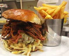 The piggyback burger - our regular cheeseburger loaded with pulled pork, bacon, slaw and pickles, served with chips