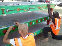Two members of the Summer Youth program paint as a part of a beautification project.