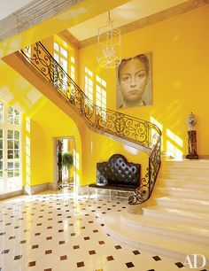 For a 17th-century-French-style mansion in Houston, interior designer Miles Redd created a powerful entrance hall that blends contemporary art and traditional architecture and furnishings into a stylish mash-up. Taxicab-yellow paint serves as the brilliant backdrop for an Eric Peters painting, a plaster chandelier by Stephen Antonson, a button-tufted bench by John Rosselli & Assoc., and a blue-and-white ceramic jar mounted on a pedestal; the metal balustrade stands out like lace.