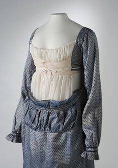 Front view of a blue silk full length Empire-line dress with the bib-front down and the bodice revealed.