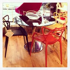 Kartell 'Masters' Polypropylene Chairs. Six colours available to see - white, grey, sage green, yellow, mustard & rusty orange.  Cattelan 'Henry' 100cm round black glass table with central pedestal.  Alessi white metal centrepiece - a stunning piece that looks like cut paper! Available at Geoffrey Drayton Epping 01992 573929