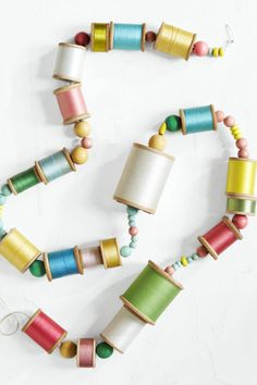 Thread spools of varying sizes and hues (interspersed with colorful wooden beads) on a long piece of embroidery thread. Knot the ends and make sure it's secure. This craft is perfect for decorating any space that needs a pop of color.