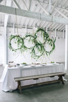 Instead of setting your centerpiece on the table, suspend a natural display from above. This winner almost looks like the Olympic rings—but with flowing ferns, tulips, and calla lilies.