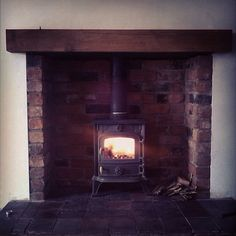 Multi fuel stove with brick lined recess, quarry tile hearth and solid oak beam - Recent installation by firesidecompany.co.uk