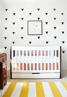 Fresh, clean, and modern DIY nursery, with black vinyl decals and pops of yellow and red.