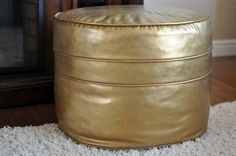 Old, vinyl pouf painted gold with Rub N Buff  via http://ss-hawker.blogspot.com