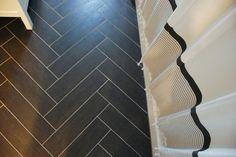 bathroom floors: tiles laid in herringbone pattern in a dark gray -- LOVE!