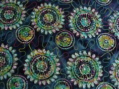 Herrlich lebensfroher und dennoch dezenter Baumwollstoff.Der Baumwollstoff wurde erst gebatikt und dann Bestickt.Der Faden der Stickerei ist in der Farbe verlaufend und zwar in den Farben gelb, türkis, grün und lila.Auf dem reinen Baumwollstoff befinden sich Kreise und schnökel.Eine Blume hat einen Durchmesser von ca. 16,5 cm.      Aus dem reinen Baumwollstoff lassen sich Blusen, Kleider, leichte Hosen, Kinderkleider, Gardinen, Kissen, Decken und vieles mehr herstellen.