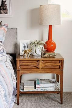 Love this mid-century nightstand and orange lamp. I might use a different pop of color in a neutral bedroom. Gold?