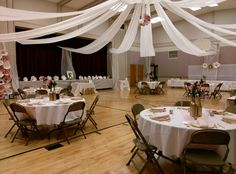 Butcher paper draped over lines paper lanterns strings of lights ceiling drapes at lds gym junglespirit Images
