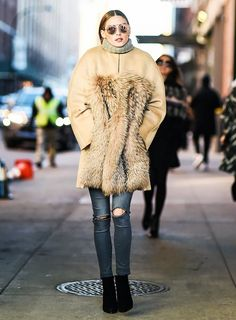 Olivia Palermo wears a turtleneck sweater, fur-trimmed coat, skinny jeans, and ankle boots