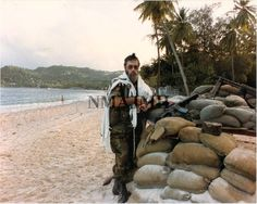 Chaplain Jacob Goldstein on beach by pile of sandbags with rifles on top. Invasion of Grenada, 1983. National Museum of American Jewish Military History