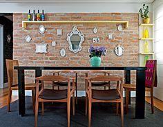 Na sala de jantar, criada pela designer de interiores Amanda Borges, a parede de tijolos é valorizada por vários espelhos, de diferentes tamanhos. O toque de cor fica por conta das garrafas decorativas, o vaso com flores e a manta sobre uma das cadeiras