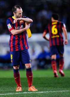 Andres Iniesta of FC Barcelona adjusts the Captain armband as his teammate Xavi Hernandez of FC Barcelona leaves the pitch during the Copa del Rey Semi Final second leg match between Real Sociedad and FC Barcelona at Anoeta Stadium on February 12, 2014 in San Sebastian, Spain.