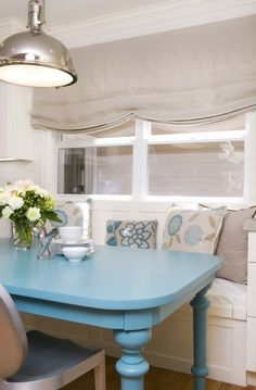 Turquoise blue  gray banquette design with soft gray silk roman shade, whimsical turquoise blue painted dining table with turned legs, white built-in bench with turquoise blue  gray floral pillows, Philippe Starck for Emeco Kong chairs and yoke pendant.