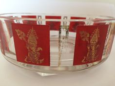 1950's Hindu Deity glass nut dish. Beautiful red and gold ink on clear glass mid century modern, this vintage dish would be a great conversion piece at your next cocktail party! This dish is free of nicks and cracks and could be used for nuts, candy, condiments or just about anything. The ink does show some wear in places but overall is in good condition considering its age.TheTravelingTortoise