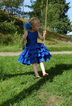 Royal blue flower girl dress with sash. Toddler girls ruffle dress in royal blue taffeta. Perfect for a boat wedding or other formal occasion. Handmade with lots of love and care.  The outer fabric is a royal blue, crash taffeta. This gives the fabric a wrinkly look. The bodice is lined with a cotton material. Buttons in the back makes this dress easy to put on, and take of. This is especially appreciated when dressing the younger children. The sash is made of the same royal blue taffeta…