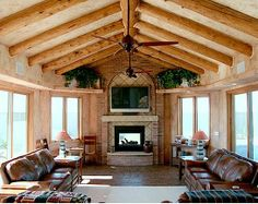 Rustic log beams complement leather couches in this stunning sunroom.