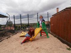 Parque infantil con arenero en el jardín.