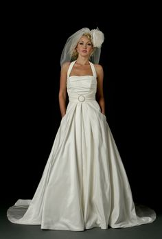 50's style wedding dress in taffeta with ruched bodice and halter neckline. Diamante buckle at waistline and diamante buttons down centre back. Full stirt has deep pockets at front.