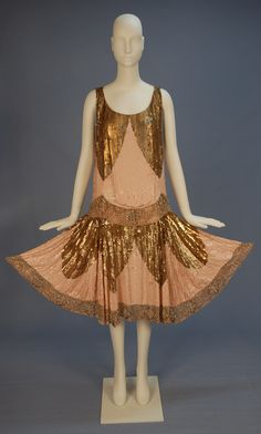 UNUSUAL BEADED and SEQUINNED ROBE de STYLE, c. 1920. Sleeveless allover sequins with large scale gold metallic scallops on pale pink ground, low scalloped wide waistband in a pattern of crystal and silver beads with sequins, the full circle skirt having matching hem band. B-42, low W-38, L-45.