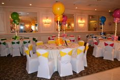Candy Land theme Sweet 16- white chair cover and multi-color sashes and 36 inch super agate balloon with lights centerpiece. looks like a big lollipop..