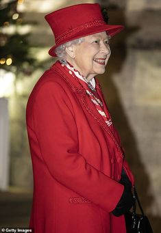 The Queen, wearing an Angela Kelly, hat and coat in Christmas red, and a ruby and diamond ...