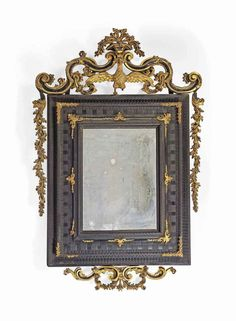 AN ITALIAN PARCEL-GILT AND EBONISED MIRROR MID-18TH CENTURY The arched foliate cresting centred by an eagle displayed supporting a vase of flowers, all flanked by festoons of foliage, above a ripple-moulded cushion frame 78¾ in. (200 cm.) high; 47 5/8 in. (121 cm.) wide