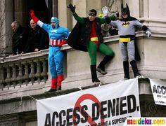Tiga orang berpakaian tokoh super hero di atas gedung terlihat tengah melakukan aksi protes.