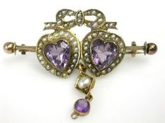 One 10 karat yellow gold double heart brooch. Two heart facetted amethysts (3.21 carats). Fifty-eight seed pearls. One amethyst (0.21 carats). Above the two joined hearts is a gold ribbon.