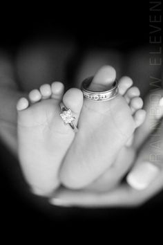 Photospiration. Baby feet held in parents hands, with wedding rings parents around toes.