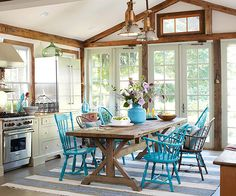 Fabulous kitchen - love the table right in the middle of the kitchen and the colorful chairs