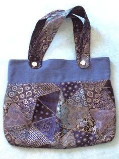 Stylish, eye-catching womens tote style hand bag. Upper band is made of blue cotton denim. The lower portion is done in a gorgeous satin finish print in multiple shades of blue with matching straps. Straps are finished with beautiful white swirled glass beads. Pleated front and back add dimension and character. Fully lined in blue denim with 2 inside pockets. A handy magnetic closure keeps your items safe. Front and back are identical.  * purse is 16 1/2 wide, 13 tall * straps 18 long, 2…