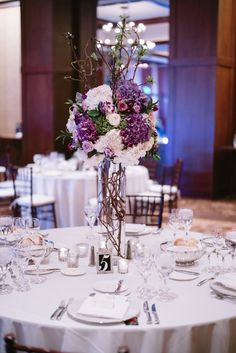 A tall floral centerpiece designed with purple hydrangea, lavender roses, white roses, white hydrangea, and blooming branches. Photography by Preston Utley and florals by www.vailvintagemagnolia.com